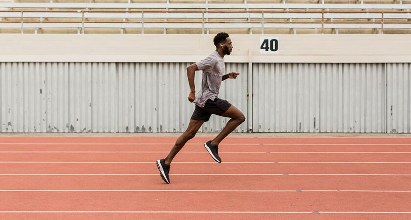 A man running on a track with the Jaybird Run XT.