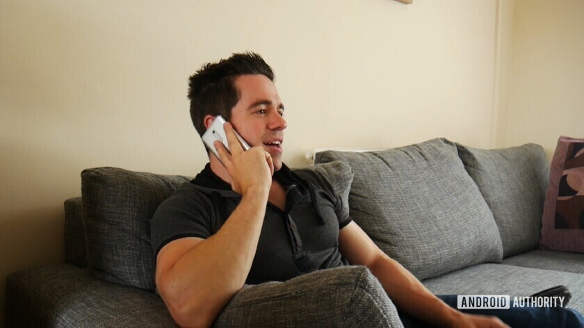 A man using a smartphone to make a phone call using his voice.
