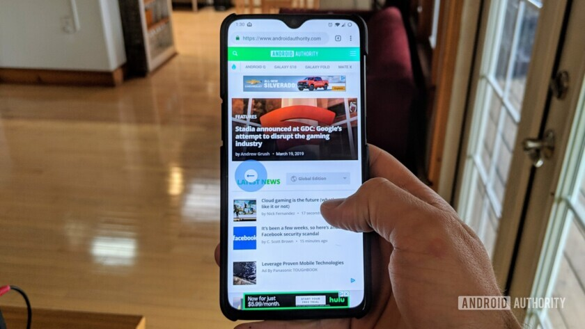 A photograph of a hand holding a smartphone demonstrating the new Chrome gestures for navigating through web pages.