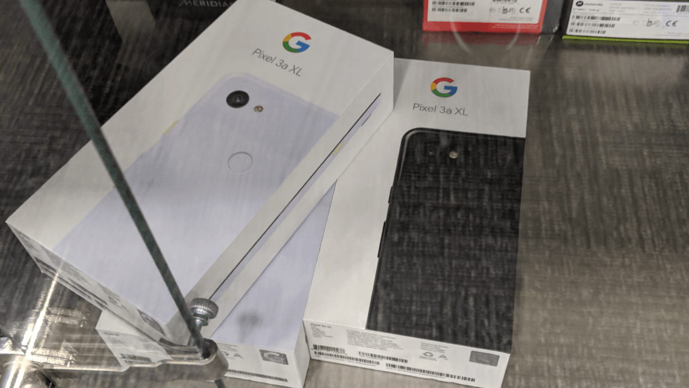 A stack of Google Pixel 3a XL boxes in a Best Buy store cabinet.