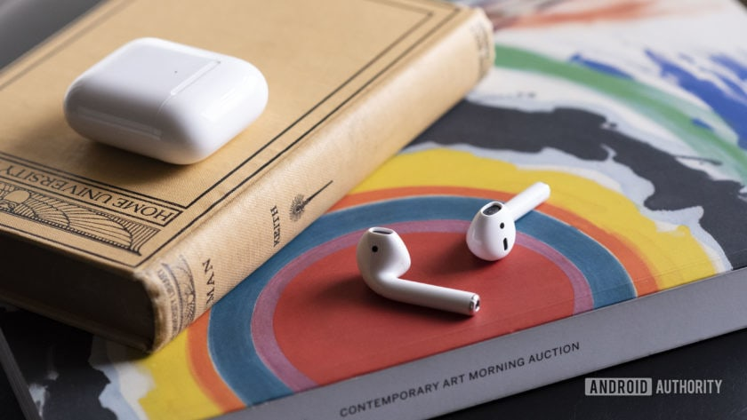 iPhone earbuds - Apple new AirPods 2 outside of the case resting on a book.
