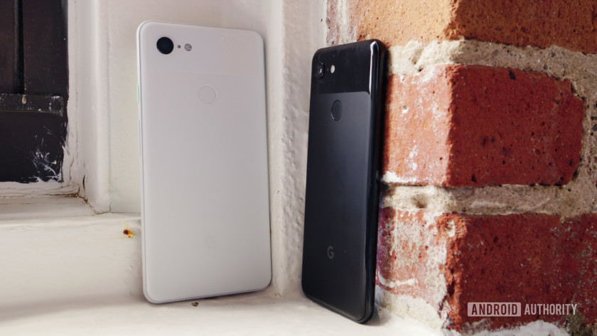 Google Pixel 3 and Pixel 3 XL stood upright outdoors against brickwork.