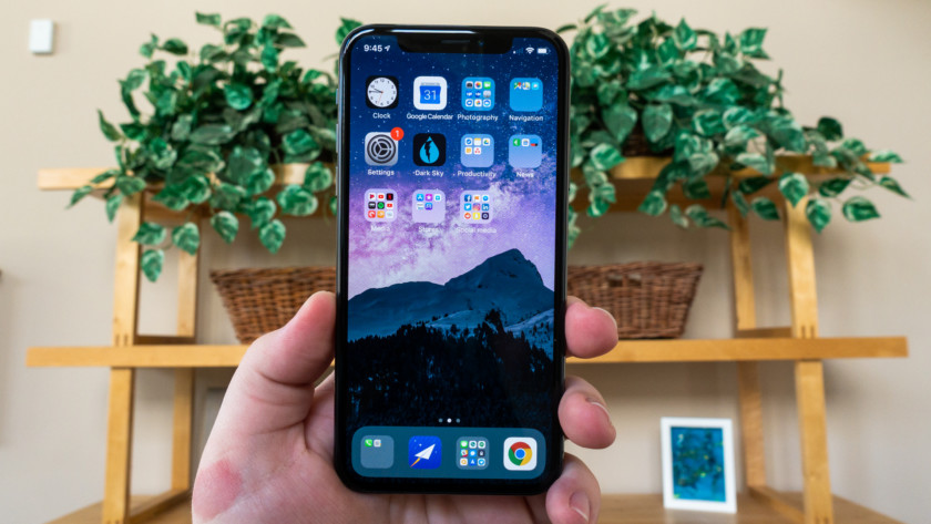 A hand holding an iPhone XS, showing off the display.