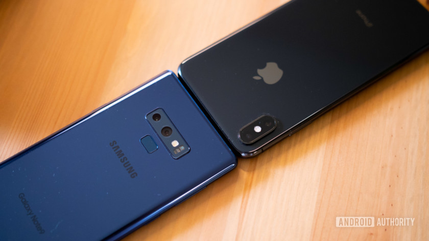A Samsung and Apple smartphone pitted head to head on a table.