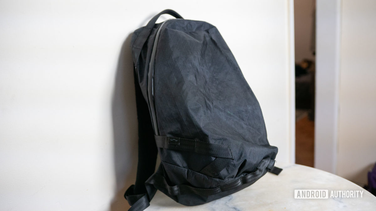 Black XPAC Able Carry Daily Backpack leaning against white wall