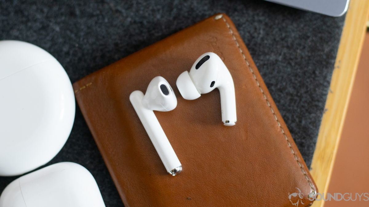 One single earbud of the AirPod Pro and Freebuds 3 side by side on a brown wallet