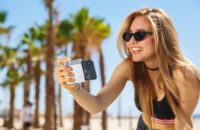 Pictar Mark II smartphone camera grip held by woman.