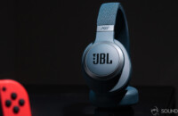 JBL Live 650BTNC Google Assistant headphones with noise cancelling on black surface with part of Nintendo Switch in the foreground.