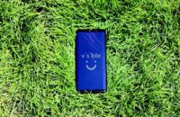 A Samsung Galaxy S9 on some grass with the Visible logo on the display.